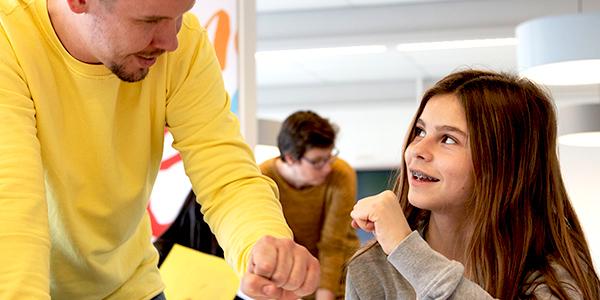 Leraar met leerling geven elkaar een high-five
